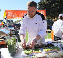 Jason finishes preparing his pork belly sandwiches for the hungry tailgating fans.
